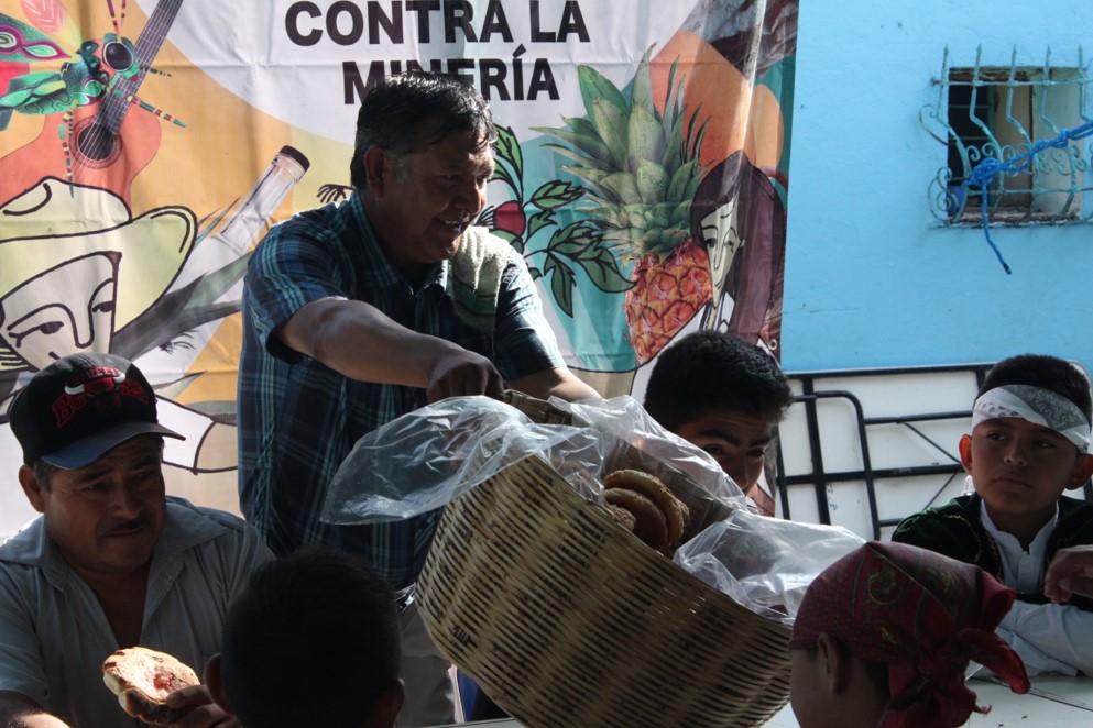 señor repartiendo pan en el compartir de la verdadera Guelaguetza contra la minería pagina 3